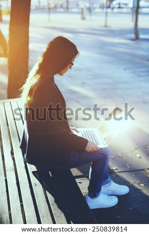 Attractive young woman using laptop outside, young student girl sitting on wood bench using laptop computer, cross process image - stock photo
