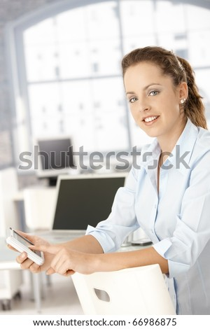 Attractive young woman using mobile in office, sitting conversed on chair.?