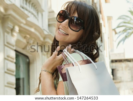 Attractive young woman walking down a shopping street in a classic city, holding shopping bags and turning around to smile at the camera.