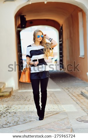 Attractive young woman walking on a street  - stock photo