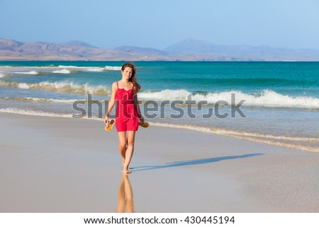 Attractive young woman walking on the beach - stock photo