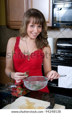 Attractive young woman washes strawberries
