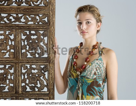 Attractive young woman wearing an exotic outfit and jewelry and leaning on a carved wood screen panel while on vacations. - stock photo