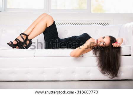 Attractive young woman wearing black dress posing on the white sofa - stock photo