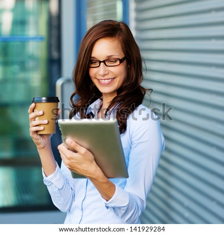 Attractive young woman wearing glasses drinking coffee and reading her touchscreen tablet while standing outside a commercial building - stock photo