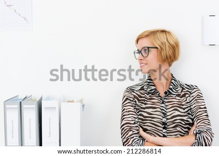 Attractive young woman wearing glasses standing with folded arms in an office looking to the side as she watches something, with copyspace - stock photo
