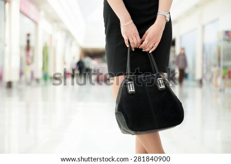 Attractive young woman wearing little black dress holding suede handbag in outlet, close-up - stock photo