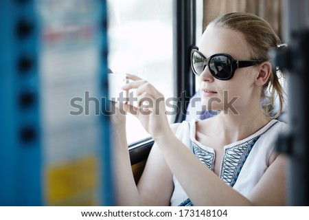 Attractive young woman wearing sunglasses holding up and photographing at her mobile on a bus or train - stock photo