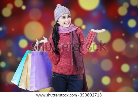 Attractive young woman wearing sweater and holding shopping bags with christmas bokeh background