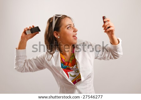 Attractive young woman wearing white jacket looking at the cellphone - stock photo