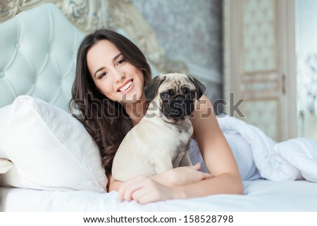 Attractive young woman wearing white pajamas is holding a dog while laying on a bed - stock photo