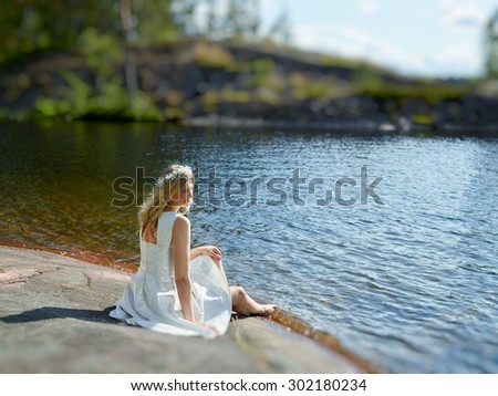 Attractive young woman wearing white summer dress, sunny summer day - blurred foreground and background - stock photo