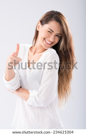 Attractive young woman winking and pointing at you - stock photo