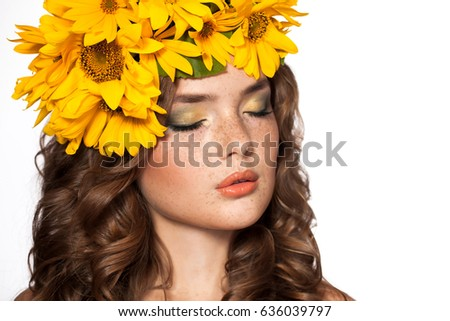 Attractive young woman with a bouquet of yellow flowers on his head. Beauty girl with curly red hair and freckles. Isolated on a white background. Color makeup, passionate lips. Closed eyes