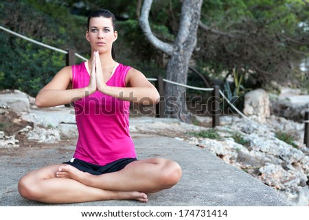 Attractive young woman with a serene expression sitting barefoot meditating in the lotus position outdoors in a park - stock photo