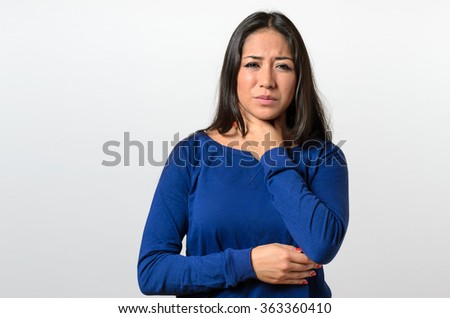 Attractive young woman with a sore throat clasping her neck with her hand and a grimace of pain as she tries to swallow - stock photo