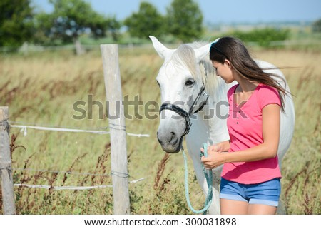 attractive young woman with beautiful camargue white and gray horse