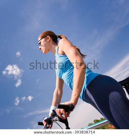Attractive young woman with bicycle against the blue sky - stock photo