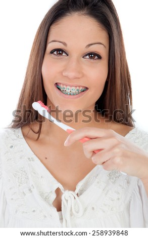 Attractive young woman with brackets cleaning her teeth isolated on a white backgroung - stock photo
