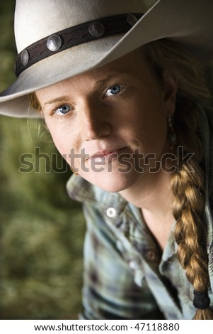 Attractive young woman with braided hair and wearing a cowboy hat. Vertical shot. - stock photo