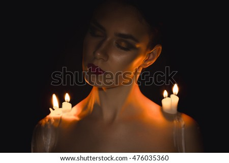 Attractive young woman with candles on her shoulders