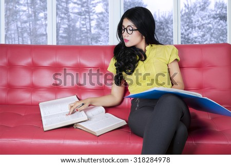 Attractive young woman with casual clothes, sitting on the sofa while reading books with winter background on the window - stock photo
