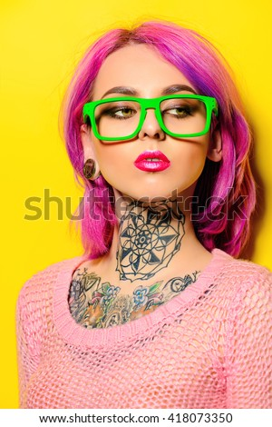 Attractive young woman with crimson hair wearing bright green glasses posing over yellow background. Bright style, fashion. Optics style. Tattoo. Hair coloring. - stock photo