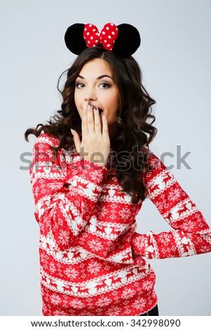 Attractive young woman, with curly dark hair, wearing in red Christmas sweater and mouse ears in her head, close her mouth by her hands, on the white background, in studio, waist up - stock photo