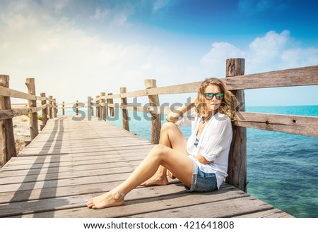 attractive young woman with curly hair  sits on a wooden bridge overlooking the ocean. Summer vacation, holiday, travel concept - stock photo