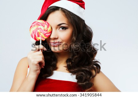 Attractive young woman, with curly hair, wearing in red santa costume, posing with colorful candy near her face, on the white background, in studio, close up