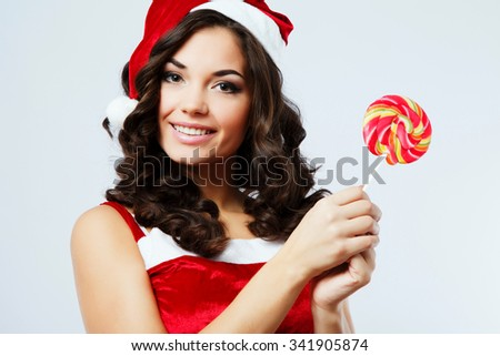 Attractive young woman, with curly hair, wearing in red santa costume, posing with colorful candy, on the white background, in studio, close up