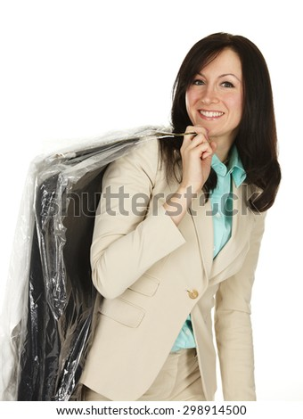 Attractive young woman with dry cleaning over her shoulder. - stock photo