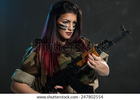 Attractive young woman with face paint on war paint in uniform holding an automatic rifle.