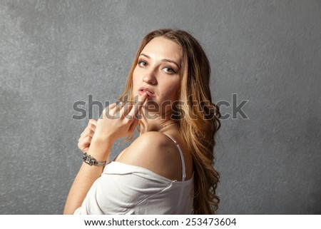 Attractive young woman with finger on lips, concept of student show quiet, silence, secret gesture, hush - stock photo