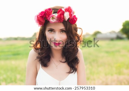 Attractive young woman with floral wreath on her head and sunset on background. Shallow DOF.