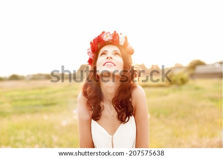 Attractive young woman with floral wreath on her head with sunset in background. Shallow DOF. Shallow contrast and lens flare due to the sunlight from the back side.Soft focused. - stock photo