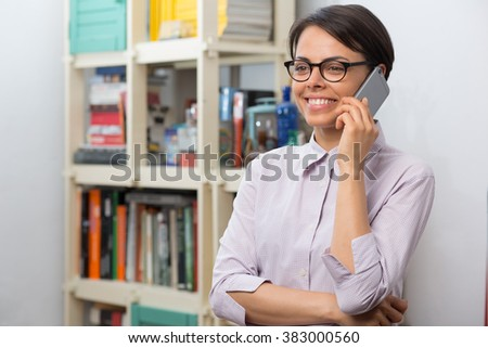 Attractive young woman with glasses talks on her smartphone