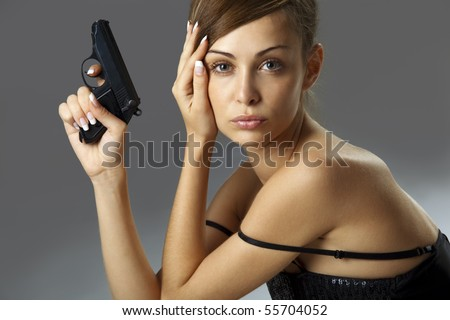 Attractive young woman with handgun over gray - stock photo