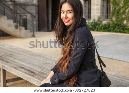 Attractive young woman with long beautiful hairs posing outdoor.