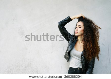 Attractive young woman with long curly hair standing against street wall background with copy space area for your text message or information. Girl looking at the copy space area - stock photo