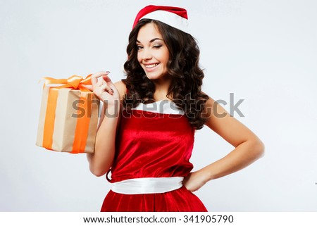 Attractive young woman, with long curly hair, wearing in red santa costume, holding present in her hand and blinking, on the white background, in studio, waist up - stock photo