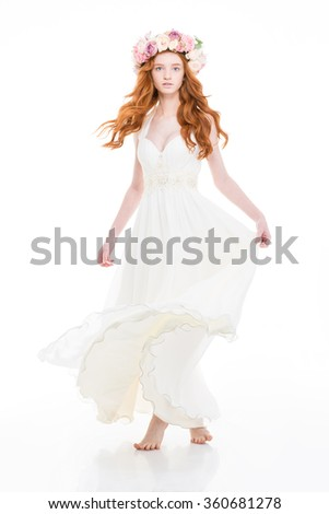 Attractive young woman with long red hair in white dress and  beautiful wreath of roses over white background - stock photo