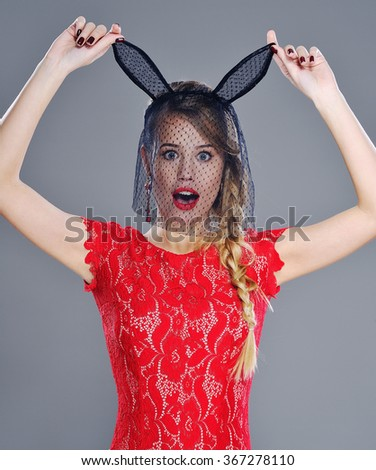 Attractive young woman with red lipstick looking surprised and holding the points of her accessory bunny ears. Beauty portrait through black veil accessory