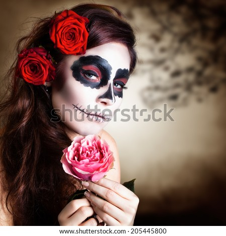 attractive young woman with sugar skull makeup - stock photo