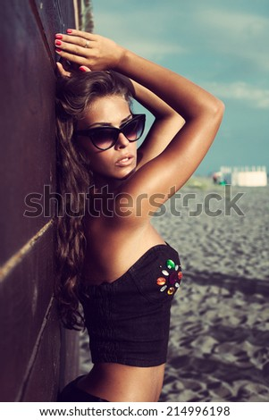 attractive young woman with sunglasses on beach sunny summer day - stock photo