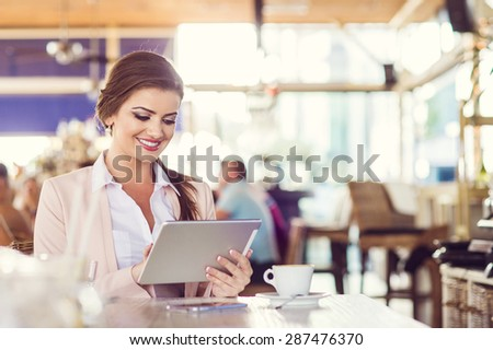 Attractive young woman with tablet in cafe - stock photo