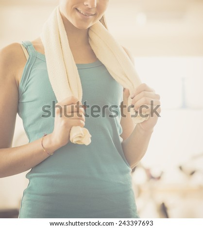 Attractive young woman with towel at gym smiling at camera.