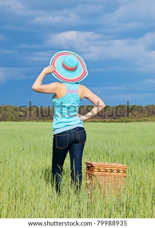 Attractive young woman with wicker basket having outdoor picnic - stock photo