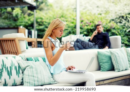 Attractive young woman working on computer, young serious man talking on mobile phone sitting in the same place on background, businesspeople and technology, sympathy of two young success people - stock photo