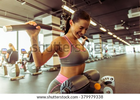 Attractive young woman working out on a fitness station in gym, pumping iron - stock photo